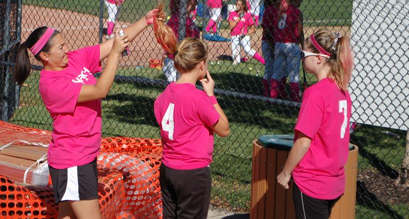 Head+softball+coach+Sara+Tani+applies+pink+hairspray+to+junior+Kristina+Meska%27s+hair+in+preparation+for+the+team%27s+%22Pink+Game%22.+Monarch+fell+11-1+to+Horizon.