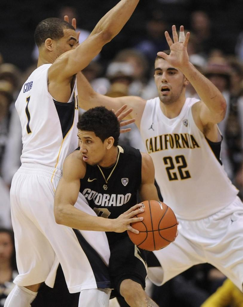 California's Justin Cobbs (1) and Harper Kamp (22) sandwich Colorado's Askia Booker in the first half of a Pac-12 Tournament semifinal at the Staples Center in Los Angeles, California, on Friday, March 9, 2012.