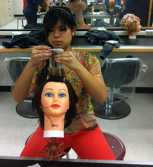 Sabrina Tran practices her styling on a mannequin in her Hairstyling 1 class at Boulder TEC.
