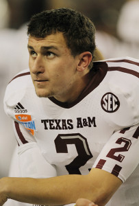 Texas A&M quarterback Johnny Manziel watches the action at the AT&T Cotton Bowl game in Cowboys Stadium in Arlington, Texas on January 24, 2013. Manziel reportedly autographed multiple pictures and had been paid for it, however there was no hard evidence of the money being paid to him. As a consequence, he was unable to play the first half of Texas A&M's first football game against Rice to start the 2013-2014 season.