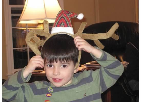 My young cousin, Ryan Realejo, poses in reindeer ears at Christmas in 2010. The Christmas outfits begin before you can even walk!