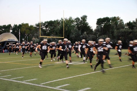 The Monarch football team runs out of the helmet at the beginning of their game against Mountain Range.