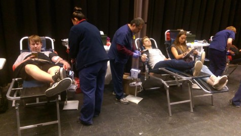 Students Michael Kasten, Simone Foreman, Jacob Kennedy donate blood at the semiannual blood drive.