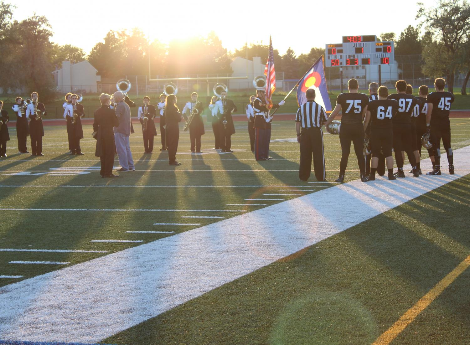 Football stands at attention while the marching band performs the National Anthem at the Aug 29 game against Longmont.