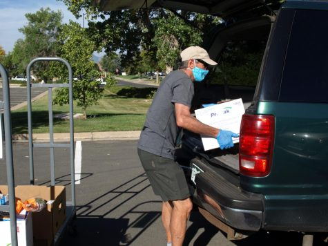 A volunteer at Community Food Share loads food into the back of a car.