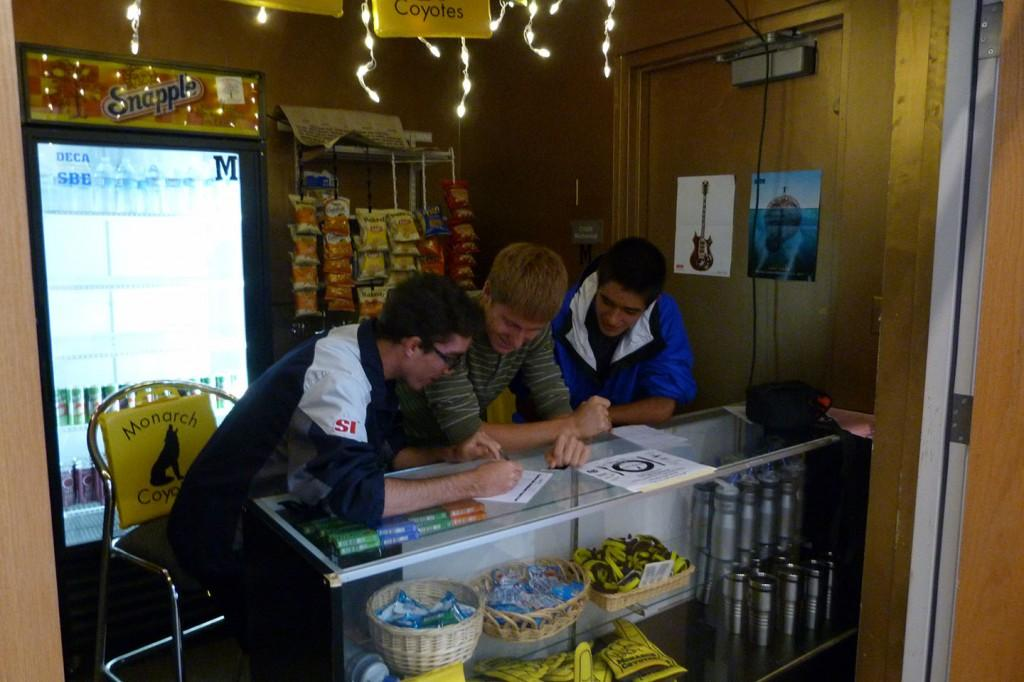 Parker Sitton (left), Daniel McComas, and Kingston Wagner huddle together to fill out paperwork at the student store during second period. (Photo credit: Conner Lund)
