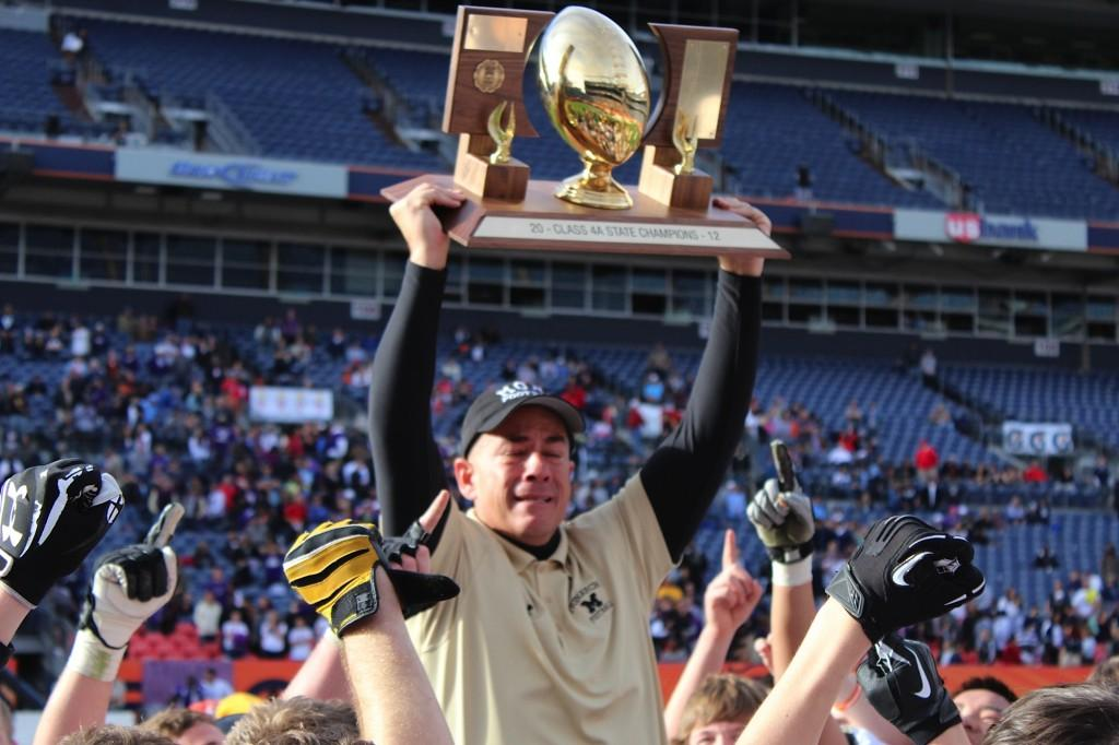 Head Coach Phil Bravo is lifted by his players while he raises the 4A State Championship trophy. The Coyotes defeated the Denver South Rebels 17-14 at Sports Authority Field at Mile High on Saturday, December 1st 2012.