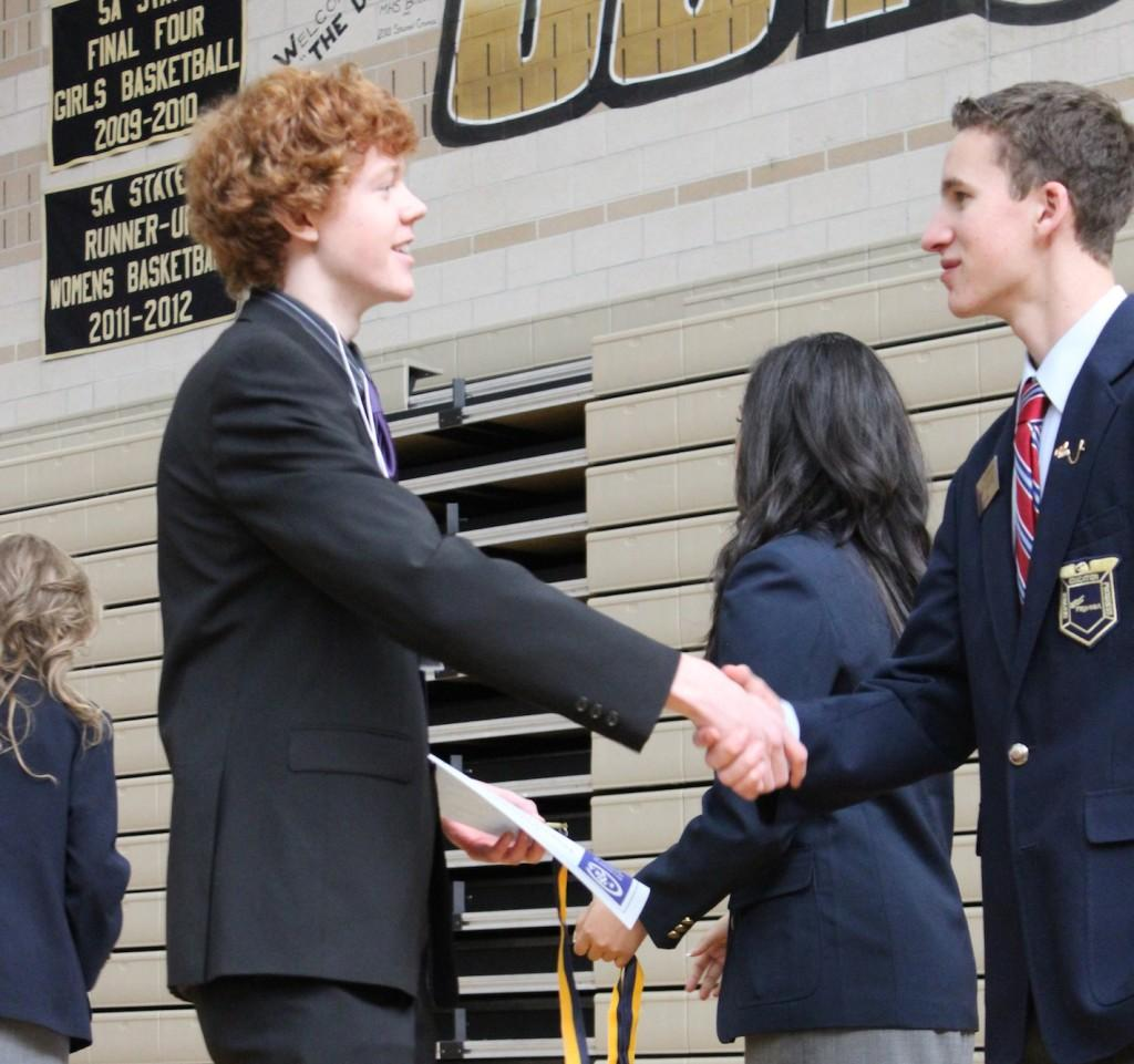 Junior Davis Conklin accepts congratulation from State Officer Cody Armstrong at the FBLA District II State Conference on February 19th, 2013 at Monarch High School.