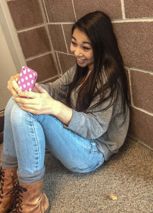 Freshman Mikaela Ichiyasu poses for a photo while sending a snapchat on her iPhone. Snapchatting has become more popular among younger generations, new users of the app surpass the amount that Facebook garners in news users, and may not be as safe or private as the company advertises.