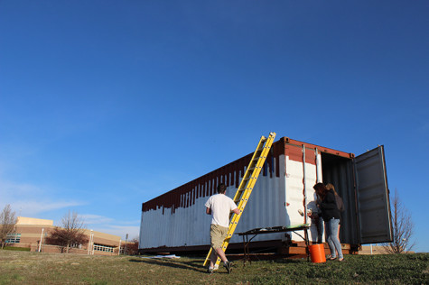 Architecture students taking the first steps in the project, painting the first layer or primer onto the container.