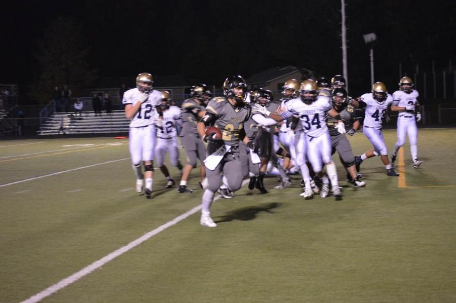 Running back Phillip Bubernak runs the ball in for an early touchdown in Friday night's game against legacy. Victory evaded Monarch after a tightly matched game with a final score of 21-28.
