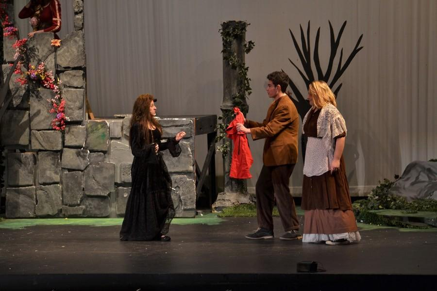 Junior Emilie Wilder Ross as the Witch reminds junior Jack Vander Veer and senior Elise Falkenstein as the Bakers to collect their