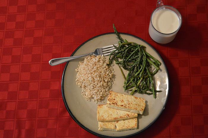 A vegan meal of tofu, brown rice, asparagus, and soy milk.