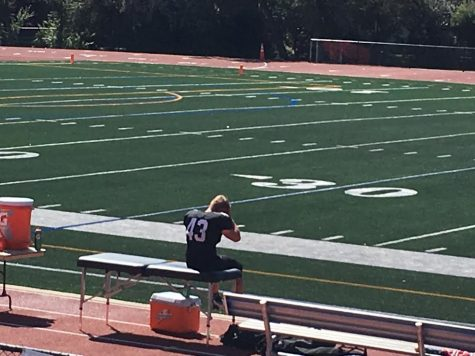 Ben Fuchs sits on the sideline after tearing his ACL against Denver South.