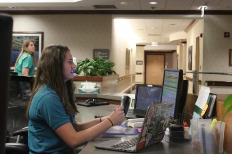 Sydney Atkinson (12) works at the front desk of the New Life Center.