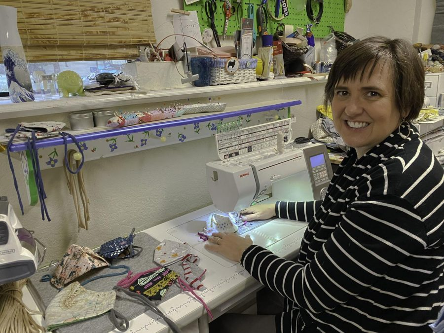 World language teacher Jenifer Farrell sews masks on her sewing machine.